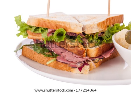 Delicious thinly sliced beef pastrami club sandwich with fresh curly lettuce served with a small dish of pickled vegetables on a white plate, isolated on white - stock photo