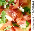 Delicious thinly sliced Italian prosciutto ham and fresh rocket leaves served as a topping on a pizza base, closeup view - stock photo