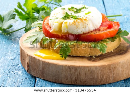 Delicious toast with poached egg, tomatoes and parsley on a thick wooden plate and a blue wooden background. Selective focus - stock photo
