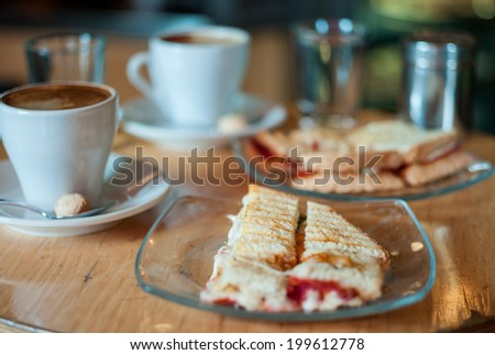 Delicious toasted mozzarella and tomato sandwich with a cup of hot coffee - stock photo