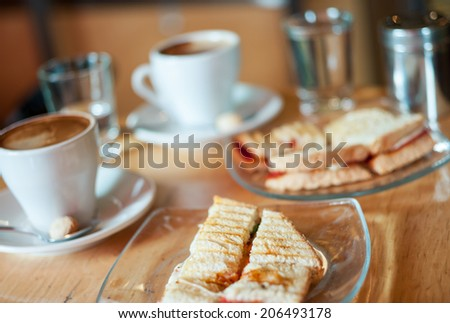 Delicious toasted mozzarella and tomato sandwich with hot coffee - stock photo
