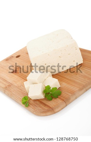 Delicious tofu background. Tofu with fresh parsley on wooden kitchen board isolated on white background. Vegan and vegetarian eating.