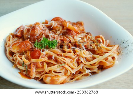 Delicious tomato pasta spaghetti with shrimps and other seafood - stock photo