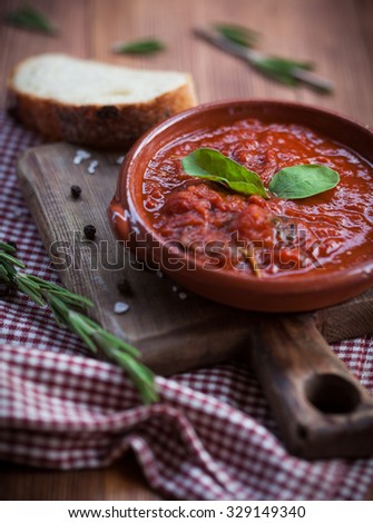 Delicious tomato soup on wooden board with basil leaf