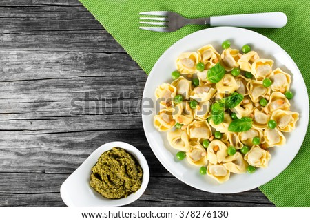 Delicious tortellini with green peas, fried Pine nuts, decorated with basil leaves on a white dish on an old rustic table, italian style. top view - stock photo
