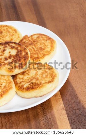 delicious traditional cheese pancakes in plate on wooden table