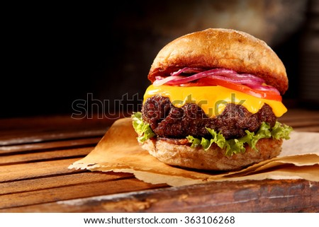 Delicious traditional cheeseburger with melted cheese and fresh salad trimmings on a juicy thick beef patty, close up low angle view with copy space - stock photo