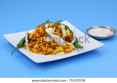 Delicious traditional Indian dish Chicken Biryani on blue background - stock photo
