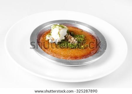 Delicious traditional Turkish dessert kunefe with pistachio powder over white background - stock photo