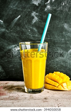 Delicious tropical mango smoothie blended with yogurt served with a straw in a tall glass with a fresh hedgehog cut mango alongside on a rustic table - stock photo