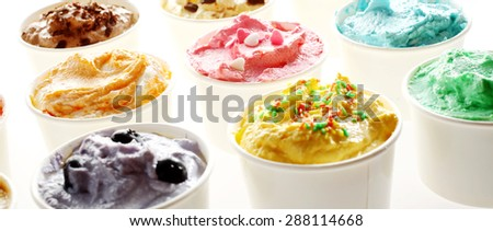 Delicious tubs of creamy summer ice cream in assorted flavours viewed low angle with blueberry, caramel and mint in the foreground over a white background - stock photo