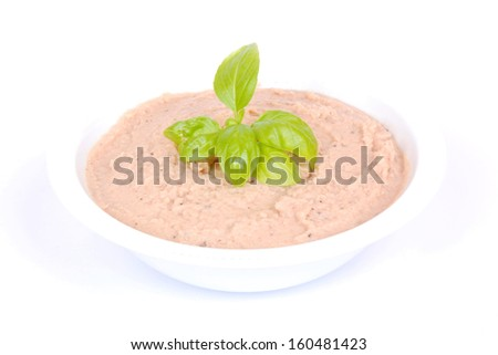 Delicious tuna fish dip garnished with basil leaves in a bowl. Image isolated on white studio background.