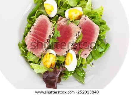 Delicious tuna steak with fresh green salad on white plate, top view isolated on white background. Culinary seafood eating.  - stock photo