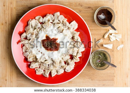 Delicious Turkish dumplings prepared and served on red plate next to seasonings in cups and chopped raw garlic - stock photo