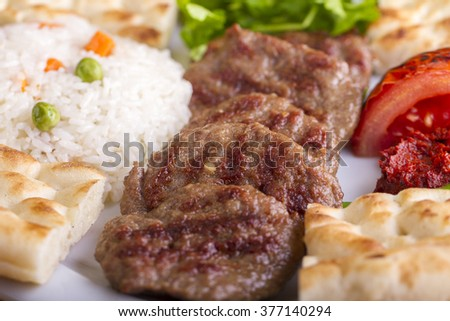 Delicious Turkish Traditional Kebab Kofte with pilaf on white plate (meatballs) - stock photo