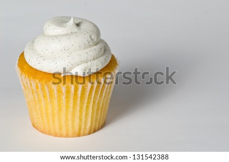 Delicious Vanilla Bean Cupcake with Black Sprinkles On White with Deep Shadow - stock photo
