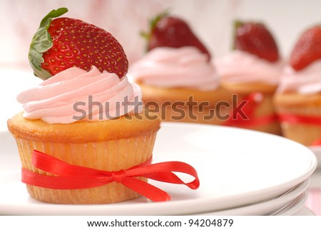 Delicious vanilla cupcake with strawberry frosting and a fresh strawberry - stock photo
