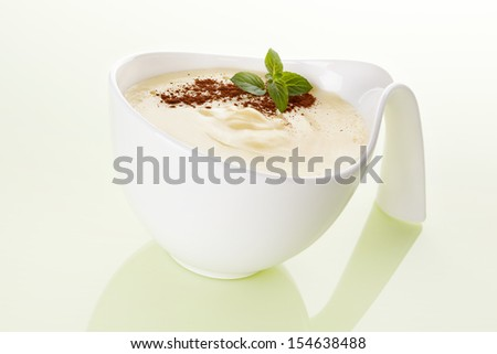 Delicious vanilla pudding with fresh mint and cocoa powder in white bowl isolated. Culinary sweet eating. - stock photo