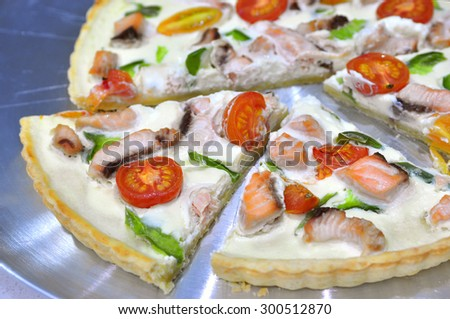 Delicious variation for quiche pie and pizza - cut pie with thickened cream cottage cheese, salmon, green capsicum cherry tomatoes cut in halves, slices aside. Selective focus, copy space, top view - stock photo