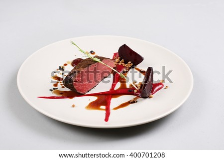 Delicious veal fillet served with sauce, molecular froth and beetroot - stock photo