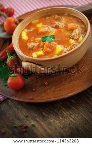 Delicious veal stew soup with meat and vegetables on wood. - stock photo