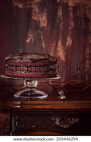 Delicious vegan chocolate cake on vintage wooden table. Selective focus. Copy space for your text. - stock photo