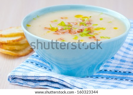 Delicious vegetable cream soup with potatoes, celery, ham, fresh herbs, homemade dinner - stock photo