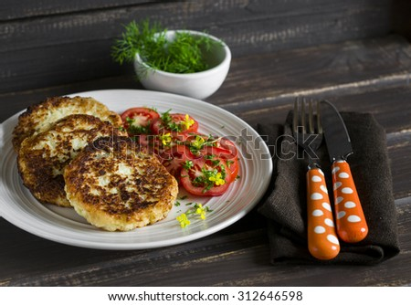 delicious vegetarian cabbage cutlets and fresh tomatoes on a light plate  on a dark wooden surface