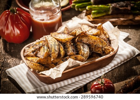 Delicious vegetarian cuisine with a platter of spicy potato wedges served with fresh tomato juice for a tasty snack or accompaniment to a summer picnic