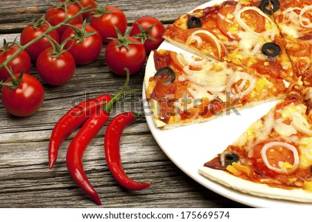 Delicious vegetarian pizza on a wooden surface - stock photo