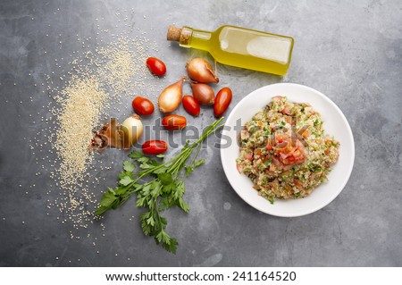 Delicious vegetarian quinoa salad with parsley, tomato and onion - stock photo