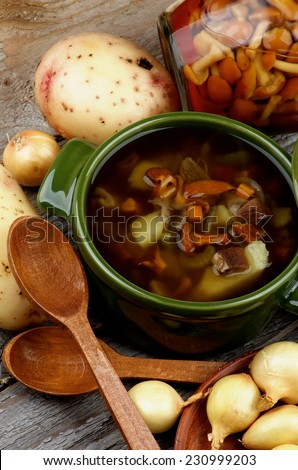 Delicious Vegetarian Soup with Chanterelle Mushrooms  in Green Pot and Raw Ingredients with Wooden Spoons on closeup Rustic Wooden background