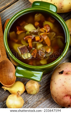 Delicious Vegetarian Soup with Chanterelle Mushrooms  in Green Pot with Raw Potato, Onions and Wooden Spoon closeup Rustic Wooden background. Top View
