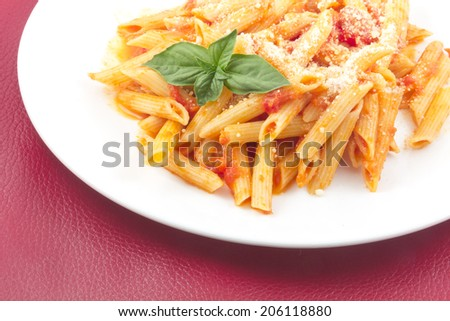 Delicious vodka penne garnished with basil leaves - stock photo