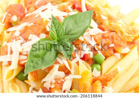 Delicious vodka penne garnished with basil leaves with peas and artichoke hearts isolated on white