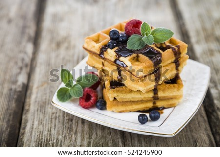 Delicious waffle with berries and chocolate on wooden table. Belgian waffles with raspberries, blueberries and mint, covered with liquid chocolate.