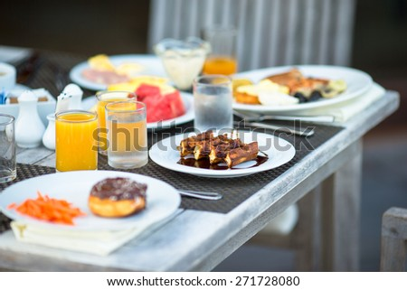 Delicious waffles, cake, coffee and juice served for breakfast at resort restaurant - stock photo