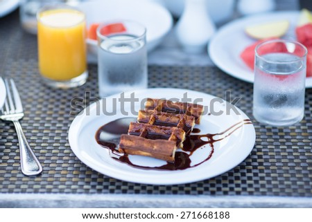 Delicious waffles, coffee and juice served for breakfast at outdoor cafe - stock photo