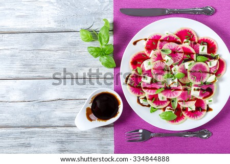 delicious watermelon radish salad with mozzarella, onion chives and basil on the white dish with caramelized balsamic vinegar in the gravy boat, top view - stock photo