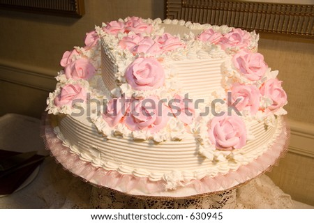 Delicious wedding cake with pink flowers, sweet white icing, vanilla cake with cherries filing.