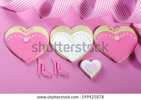 Delicious wedding party bride and bridesmaids pink and white heart shape biscuit cookies bridal table favors with high heel shoes on pink background. - stock photo