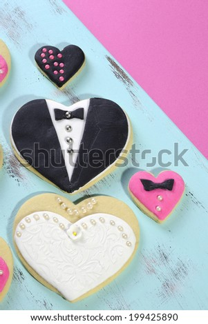 Delicious wedding party bride and groom pink, white and black heart shape biscuit cookies bridal table favors with mini decorated hearts on a vintage blue tray and pink background. - stock photo