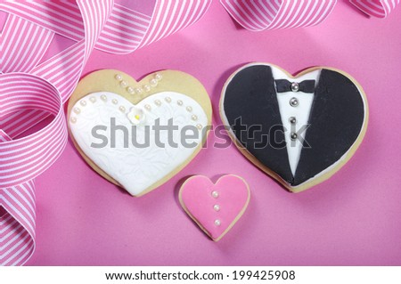Delicious wedding party bride and groom pink, white and black heart shape biscuit cookies bridal table favors against a pink background. - stock photo