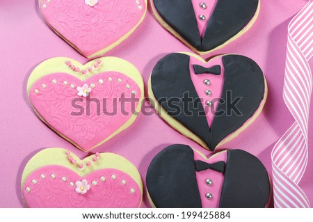 Delicious wedding party bridesmaids and groomsmen pink, white and black heart shape biscuit cookies bridal table favors on pink background. Close up. - stock photo
