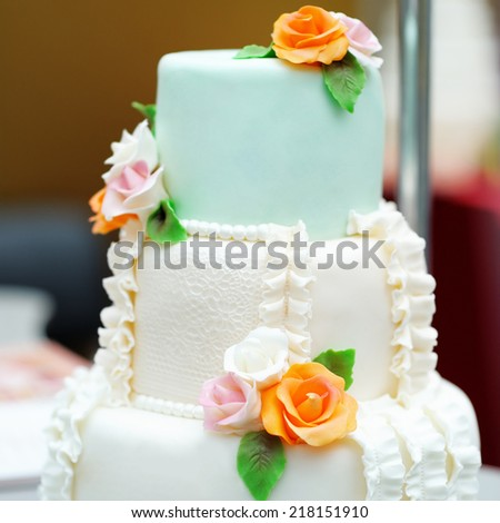Delicious white and green wedding cake decorated orange cream roses - stock photo
