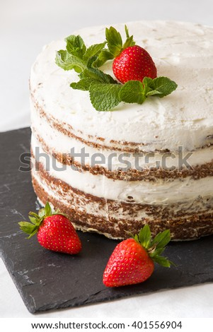 Delicious white cream icing cake with strawberry on the black board. Naked cake with cream, decorated with strawberries and mint. Naked cake - stock photo