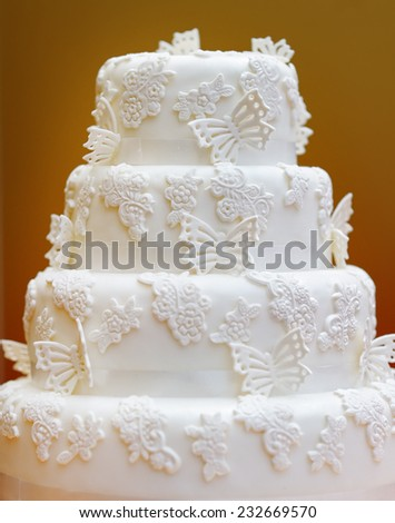 Delicious white wedding cake decorated with butterfly  - stock photo