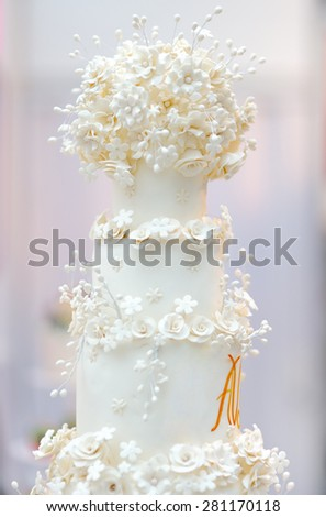 Delicious white wedding cake decorated with cream flowers - stock photo
