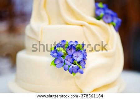 Delicious white wedding or birthday cake decorated with flowers  - stock photo