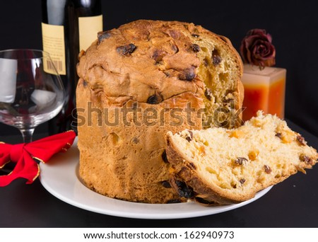Delicious whole panettone, Christmas cake with glass, red wine, candle, dried red rose, and decoration bow on black background.